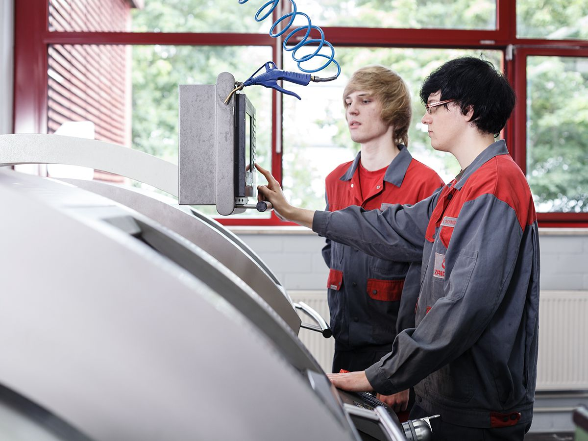 2 Personen an einer Maschine - Maschinenführung